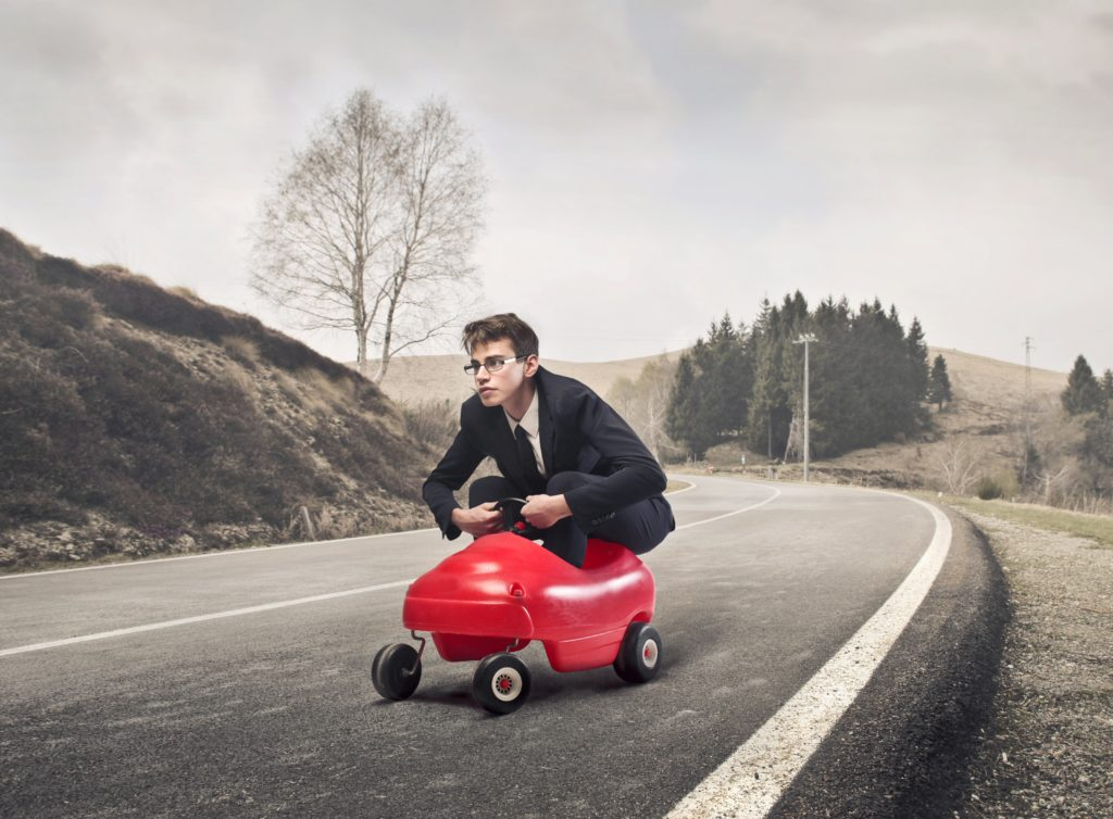 professional-looking guy riding in a toy car
