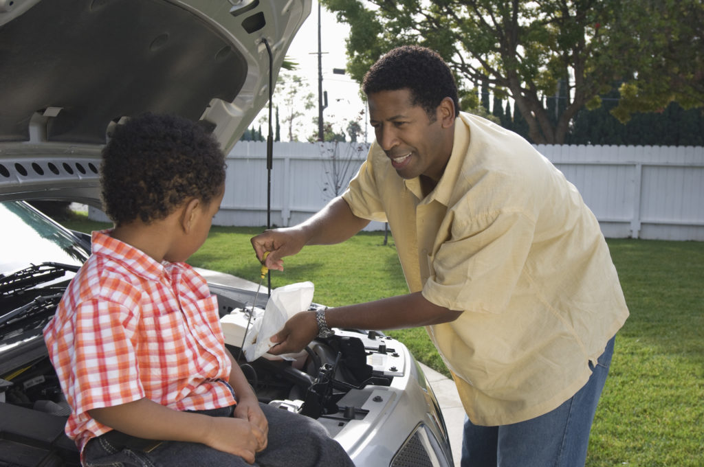 a son helping his dad change the car's oil