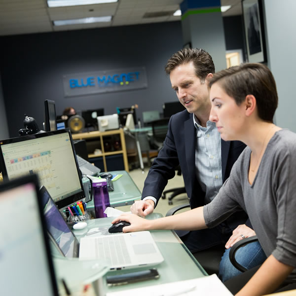 two digital marketers discuss strategy in front of a laptop