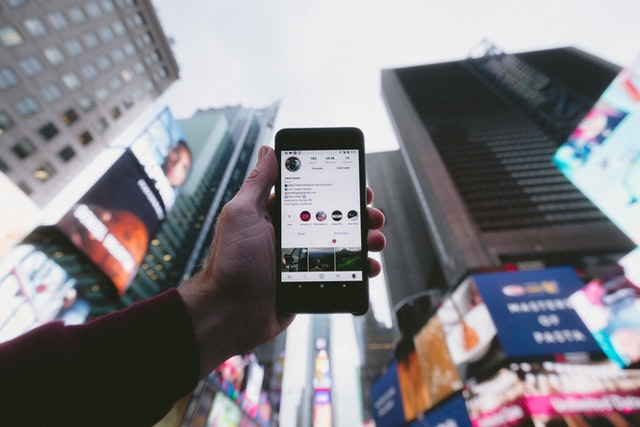hand holding up smartphone with instagram in Times Square NYC