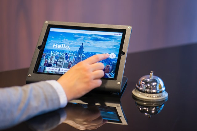 guest checking into a hotel using a tablet at the front desk